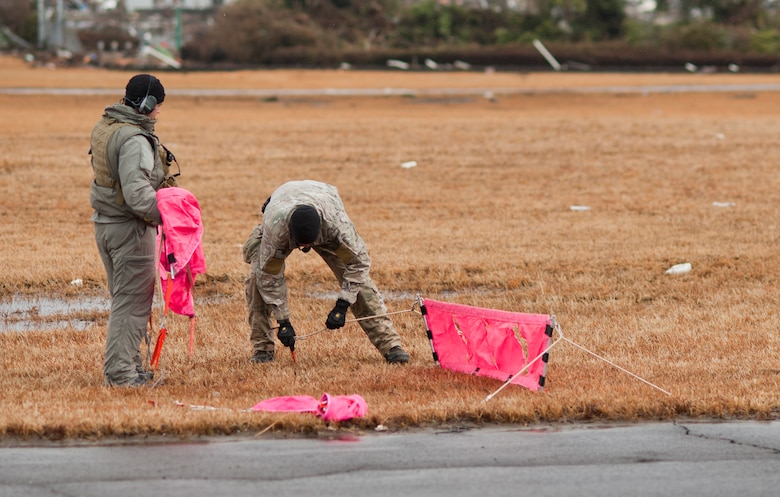 SENDAI AIRPORT, Japan -- Combat controllers from the 320th Special Tactics Squadron set up flightline markers to inform pilots of the useable space on the runway here March 16. Members of the 320th STS, stationed out of Kadena Air Base, deployed to Sendai Airport to help clear the runway and make it ready for fixed-wing aircraft traffic. (U.S. Air Force photo/Staff Sgt. Samuel Morse)
