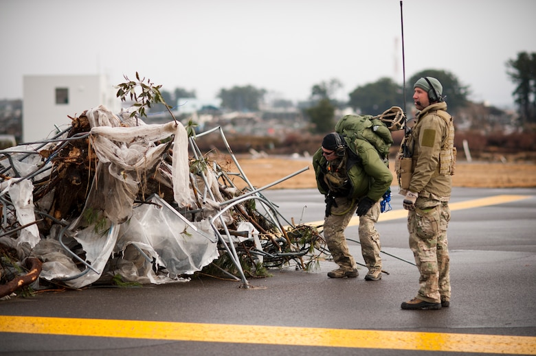 SENDAI AIRPORT, Japan -- Airmen from the 320th Special Tactics Squadron assess debris on the runway here March 16. Members of the 320th STS, stationed out of Kadena Air Base, deployed to Sendai Airport to help clear the runway and make it ready for fixed-wing aircraft traffic. (U.S. Air Force photo / Staff Sgt. Samuel Morse)