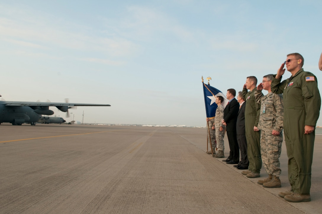 Members of the 136th Airlift Wing along with Mr. John Wood, North Texas Regional Director for Senator John Cornyn and Mr. Charles Boswell, representing State Senator Wendy Davis give honor to those deploying in support of Operation Enduring Freedom aboard the C-130H from the wing. The deployers will be supporting the 774th Expeditionary Airlift Squadron in both air and ground operations. (U.S. Air Force photo by Senior Master Sgt. Elizabeth Gilbert/released)