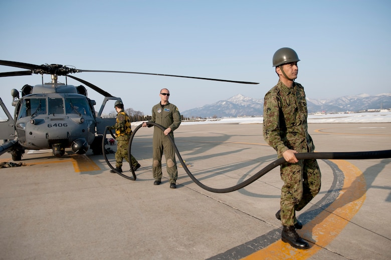 Tech. Sgt. Michael Wells and members of the Japan Ground Self-Defense Force refuel an HH-60 Pave Hawk helicopter March 13, 2011, at Yamagata, Japan. Yamagata is a fuel staging area in support of Japan's earthquake and tsunami recovery efforts. Sergeant Wells is an aerial gunner assigned to the 33rd Rescue Squadron. (U.S. Air Force photo/Staff Sgt. Samuel Morse)