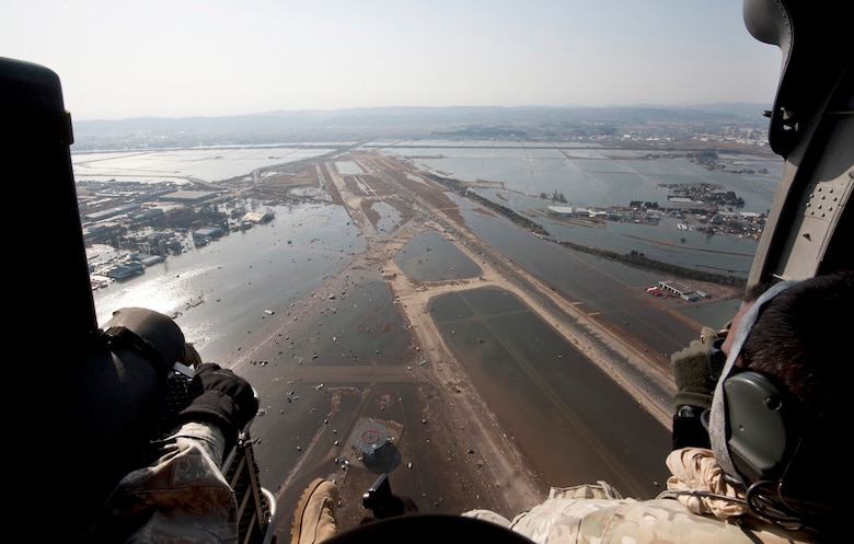 Airmen and Marines fly over the Sendai Airport, Japan, March 13, 2011, to survey the aftermath of the 8.9-magnitude earthquake and subsequent tsunami that struck the region. The small dots covering the runway are vehicles left there after the tsunami water receded. The service members are airlift and rescue leaders assisting with Japan's earthquake and tsunami recovery effort. (U.S. Air Force photo/Staff Sgt. Samuel Morse)