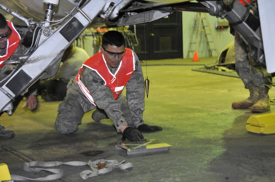 Staff Sgt. Wesley Hammond, an aircraft maintenance technician assigned to the 129th Maintenance Squadron, observes a plumb bob that indicates the position and balance of TF-104G aircraft as it is slowly raised by airbags under the aircraft. Airmen from the 129th Rescue Wing conducted a full-scale airbag lift exercise using a TF-104G static display to simulate a downed aircraft at Moffett Federal Airfield, Calif., Mar. 15, 2011.  (Air National Guard photo by Tech. Sgt. Ray Aquino/RELEASED)