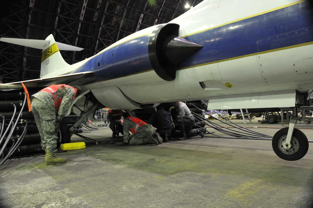 Aircraft maintenance personnel assigned to the 129th Maintenance Squadron inspect the main landing gears of a TF-104G for leaks and discrepancies. Airmen from the 129th Rescue Wing conducted a full-scale airbag lift exercise using a TF-104G static display to simulate a downed aircraft at Moffett Federal Airfield, Calif., Mar.