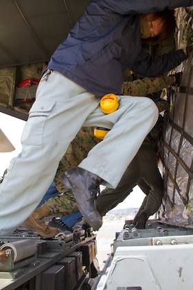 Japanese workers, along with Marines and sailors push pallets of food into a C-130T from Fleet Logistics Support Squadron 62, Naval Air Station Jacksonville, Fla., that will be flown to Misawa Air Base for humanitarian aid in support of Operation Tomodachi here March 18.