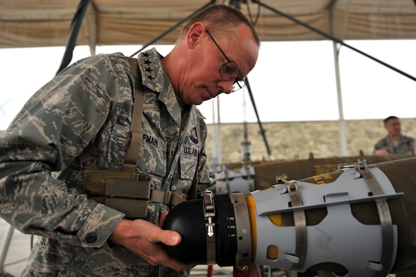 Gen. Donald Hoffman, Air Force Materiel Command commander, installs a nose fuse on a GBU-54 during his visit at the ammunition supply point at Bagram Airfield, Afghanistan, March 18, 2011. General Hoffman received  hands-on training on how to build a live bomb. (U.S. Air Force photo by Senior Airman Sheila deVera)