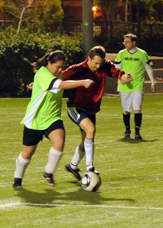 A player from the Los Angeles AFB co-ed soccer team battles a player from the 1-800-GOT-Junk team for control of the ball during a match, March11.  LAAFB won the match 8-3.  (Photo by Jim Gordon)