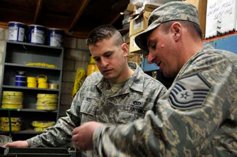 SAN CLEMENTE ISLAND, Calif -- Master Sgt. Tom Bradley, an electrical supervisor with the 176th Civil Engineer Squadron, teaches some tools of the trade to Senior Airman John Buso, an electrician from the unit.In March 2011, the 176 CES deployed to this remote location off the coast of southern California for two weeks to train and work on a variety of infrastructure projects. Alaska Air National Guard photo by Staff Sgt. N. Alicia Goldberger.