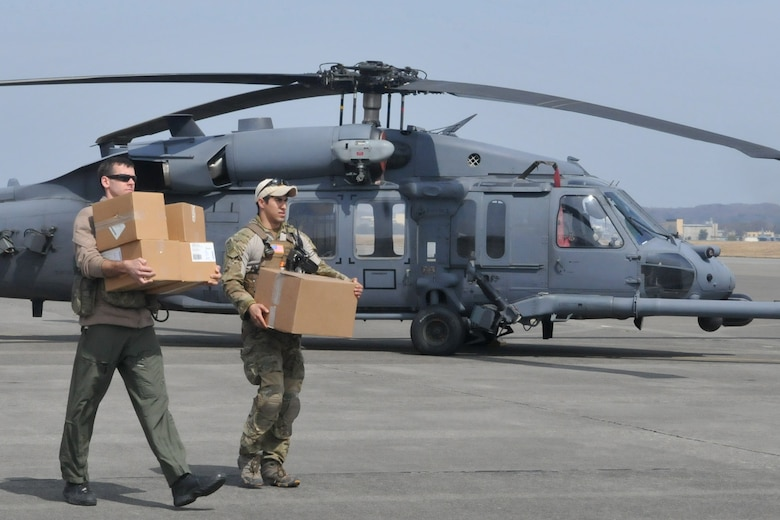 YOKOTA AIR BASE, Japan -- Two airmen carry medical supplies to an HH-60 prior to take off here, March 20. The 33rd Rescue Squadron successfully transported supplies to displaced peoples in Kessenuma City, in support of Operation Tomodachi. Kessenuma experienced massive destruction from the earthquake and tsunami in northeastern Japan, March 11. (U.S. Air Force photo/2nd Lt. Christopher Love)