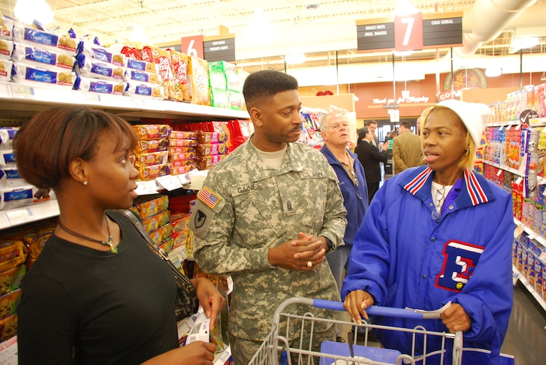 FORT LEE, Va. – Command Sgt. Maj. John M. Gaines Jr. talks to two military family members during the grand opening of the commissary at Naval Air Station Joint Reserve Base, New Orleans on Feb. 8. Sgt. Maj Gaines is the senior enlisted advisor to the Defense Commissary Agency director. (Defense Commissary Agency photo/ Rick Brink)