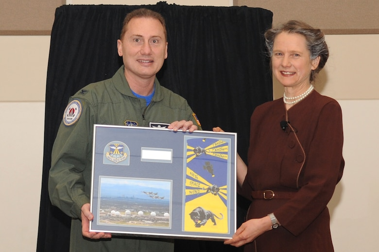 BUCKLEY AIR FORCE BASE, Colo.-- Col. Clint Crosier, 460th Space Wing commander, presents an memento to Susan Marie Frontczack March 18, 2011. Susan Marie Frontczack has won more the 5 awards as a traveling Storysmith. (U.S. Air Force photo by Airman Manisha Vasquez)