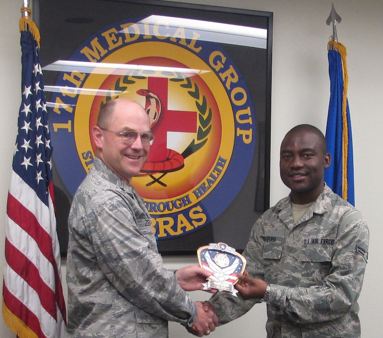 GOODFELLOW AIR FORSE BASE, Texas--Airman 1st Class John Ndubusi, Medical Support Squadron, receives the Airman of the Fourth Quarter award for the MDSS, July 2010 from Lt. Col. David Zemkosky, previous MDSS Commander. (courtesy photo)