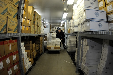 Surrounded by hundreds of frozen boxes in a 20-degree walk-in freezer, Culinary Specialist 2nd Class David Haeffner stacks frozen foods during a store's on-load at the Joint Base Charleston-Weapons Station Galley, Mar. 17.