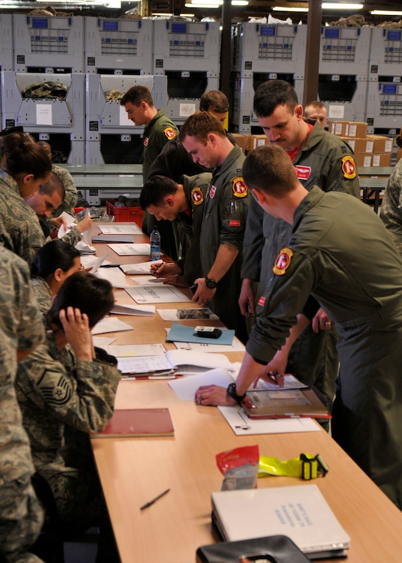 SPANGDAHLEM AIR BASE, Germany— Pilots from the 480th Fighter Squadron process through the Personnel Deployment Function line in preparation of Operation Odyssey Dawn March 18. Joint Task Force Odyssey Dawn is the U.S. Africa Command task force established to provide operational and tactical command and control of U.S. military forces supporting the international response to the unrest in Libya and enforcement of United Nations Security Council Resolution (UNSCR) 1973. UNSCR 1973 authorizes all necessary measures to protect civilians in Libya under threat of attack by Qadhafi regime forces.  JTF Odyssey Dawn is commanded by U.S. Navy Admiral Samuel J. Locklear, III. (U.S. Air Force photo/Airman 1st Class Brittney Frees)