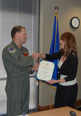 NELLIS AIR FORCE BASE, Nev. -- (Right) Michele Baker, 926th Group budget officer, is presented with a certificate of service for 20 years of service in the government of the United States by Col. Herman Brunke, 926th GP commander, March 16. (U.S. Air Force photo/Capt. Jessica Martin)