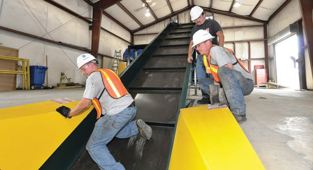 Vick Hobarter, top right, with International Baler, watches as Jay Thurmond, right, and Wyatt James, left, with Recycling Equipment Inc., (REI, Inc.), help to install the conveyer for a newly acquired SST series baler made by International Baler at AEDC's recycling center. (Photo by: Rick Goodfriend)