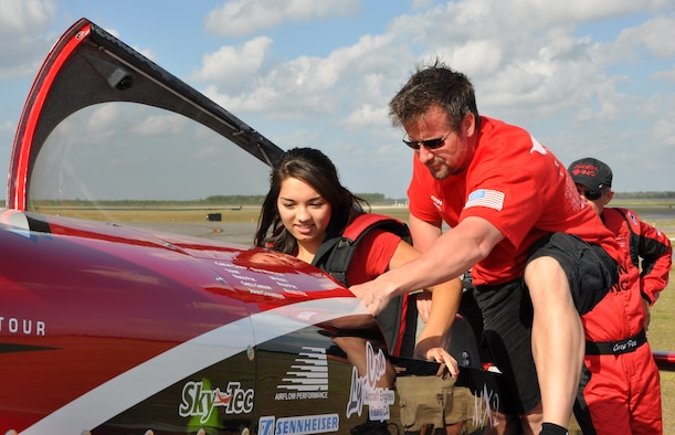 Dax Wanless, vice president of operations and a pilot with Greg Poe Airshows, helps Nicole Goetz, 17, prepare for her flight in the ethanol-powered Fagen MXS with Greg Poe March 23. Nicole was recently selected as the United States Air Force Military Child of the Year and was awarded a flight in air show performer Greg Poe's aerobatic airplane. (U.S. Air Force photo by Airman 1st Class Christopher Reel)