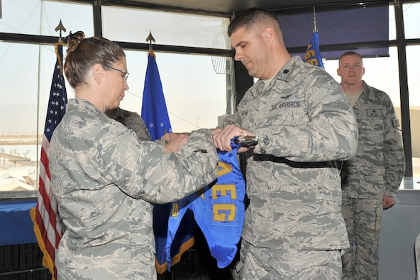 Col. Lesa Toler, 466th Air Expeditionary Group commander, and Lt. Col. Jeffrey Collins, 766th  Air Expeditionary Squadron commander, rolls the guidon as Lt. Col. Collins relinquishes command during the 766th AES inactivation ceremony at Bagram Airfield, Afghanistan, March 23, 2011. Colonel Collins will assume command of the 966th Air Expeditionary Squadron. (U.S. Air Force photo by Senior Airman Sheila deVera)