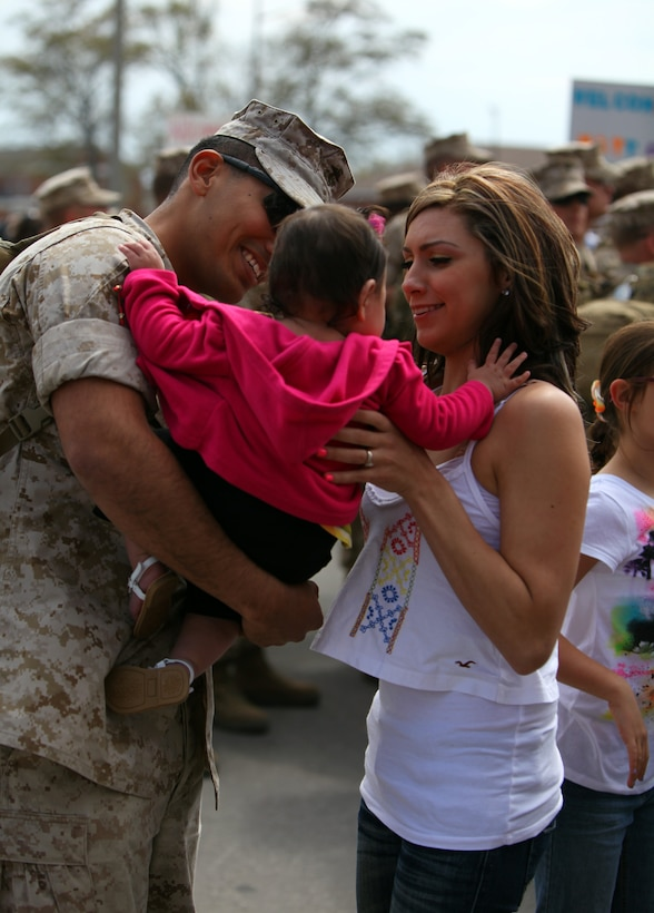 A Marine with Weapons Company, 1st Battalion, 8th Marine Regiment, 2nd Marine Division, embraces his daughter and wife aboard Marine Corps Base Camp Lejeune N.C., during a welcome home ceremony March 25, 2011. The unit has returned after a seven-month deployment to Helmand Province, Afghanistan, in support of Operation Enduring Freedom.