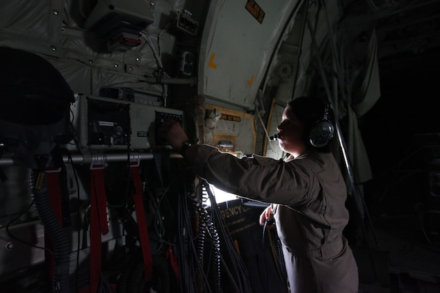 Cpl. Jessica M. Egan, a crew chief with Marine Aerial Refueler Transport Squadron 352, adjusts the communication system on the Harvest Hawk equipped KC-130J after taking off from Camp Dwyer, Afghanistan, march 25. The one-of-a-kind Harvest Hawk system includes a version of the target sight sensor used on the AH-1Z Cobra attack helicopter as well as a complement of four AGM-114 Hellfire and 10 Griffin missiles. This unique variant of the KC-130J supports 2nd Marine Aircraft Wing (Forward) in providing closer air support and surveillance for coalition troops on the ground in southwestern Afghanistan.