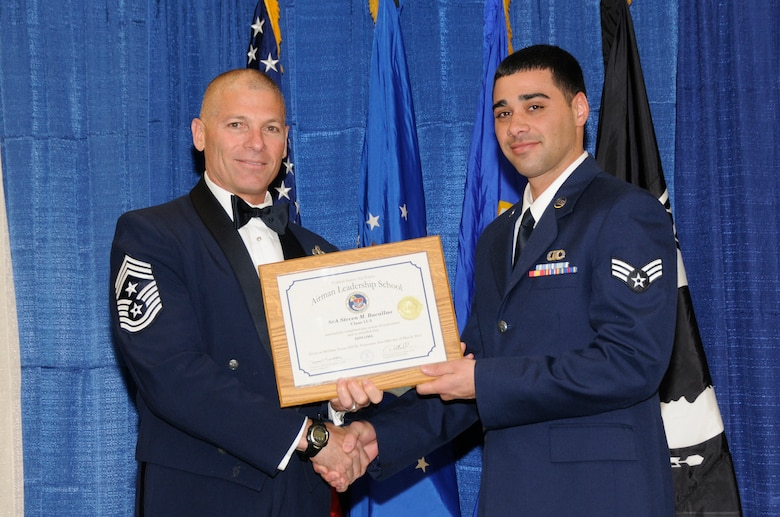 McGHEE TYSON AIR NATIONAL GUARD BASE, Tenn. - Senior Airman Steven M. Bacallao, right, an air traffic control specialist with the Wisconsin Air National Guard, receives the distinguished graduate award for Airman Leadership School Class 11-3 at The I.G. Brown Air National Guard Training and Education Center from Louisiana Command Chief Master Sgt. James E. Downing, Sr., March 24, 2011.  The distinguished graduate award is presented to students in the top ten percent of the class.  It is based on objective and performance evaluations, demonstrated leadership, and performance as a team player. (U.S. Air Force photo by Master Sgt. Kurt Skoglund/Released)