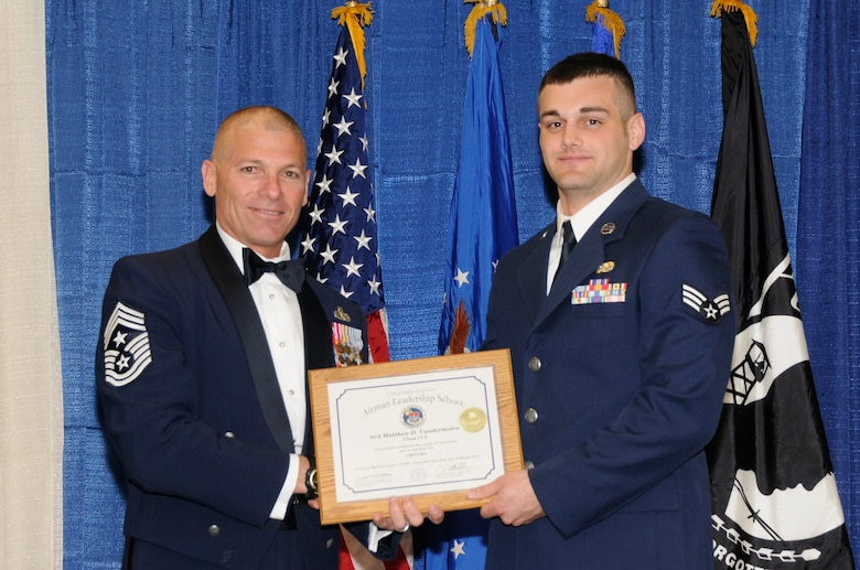 McGHEE TYSON AIR NATIONAL GUARD BASE, Tenn. - Senior Airman Matthew D. Vandermolen, right, a cyber systems operations journeyman with the Illinois Air National Guard, receives the distinguished graduate award for Airman Leadership School Class 11-3 at The I.G. Brown Air National Guard Training and Education Center from Louisiana Command Chief Master Sgt. James E. Downing, Sr., March 24, 2011.  The distinguished graduate award is presented to students in the top ten percent of the class.  It is based on objective and performance evaluations, demonstrated leadership, and performance as a team player. (U.S. Air Force photo by Master Sgt. Kurt Skoglund/Released)