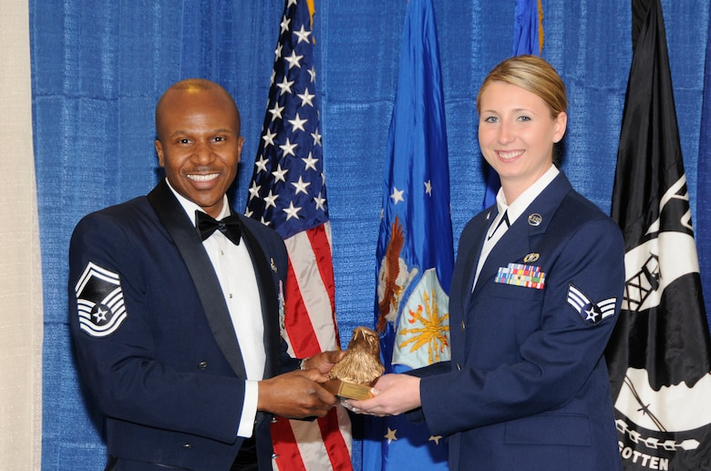 McGHEE TYSON AIR NATIONAL GUARD BASE, Tenn. - Senior Airman Casandra J. Pohlen, right, a civil engineer apprentice with the Minnesota Air National Guard, receives the academic achievement award for Airman Leadership School Class 11-3 at The I.G. Brown Air National Guard Training and Education Center from Senior Master Sgt. Tyrone Bingham, EPME Director of Education, March 24, 2011.  The academic achievement award denotes excellence as a scholar. It is based upon all summative objective tests and individual performance evaluations and is given to the student with the highest overall academic standing. (U.S. Air Force photo by Master Sgt. Kurt Skoglund/Released)