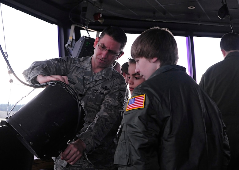 Master Sgt. Tracy Truman, 62nd Operations Support Squadron, demonstrates to 14-year-old 'Pilot for a Day' Josh Loux and his friend, Mac Davis, how a light-gun operates during a tour of the McChord Field control tower March 18, 2011, at Joint Base Lewis-McChord, Wash.  (U.S. Air Force photo/Adamarie Lewis-Page)