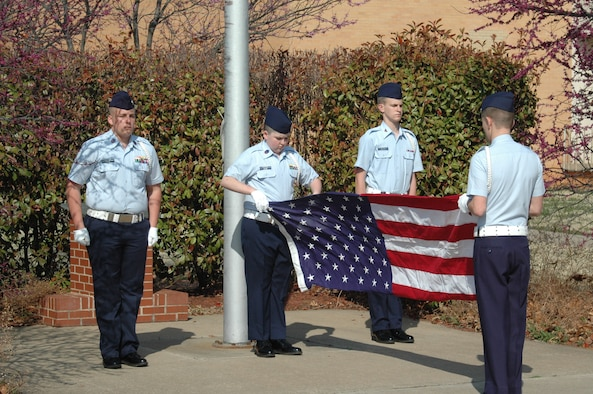 The Grove Composite Squadron team members, from left, Cadets Chief Master Sgt. Benjamin Goodman, Senior Master Sgts. Dakota Gray and Marshall Cook and Senior Airman Justus Taylor demonstrate their ability to lower and fold American flag for this part of the competition. (Air Force photo by Kathy Paine)