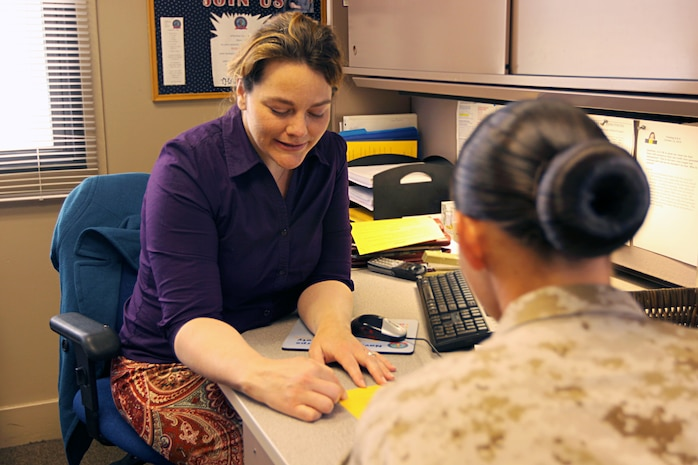 Jeanette Waddell, relief services assistant, Navy Marine Corps Relief Society, gives financial advice to a Marine at Camp Pendleton's NMCRS facility. The non-profit organization assists active duty and retired Marines, sailors and their families with interest-free loans and grants when they are in need of financial aid.