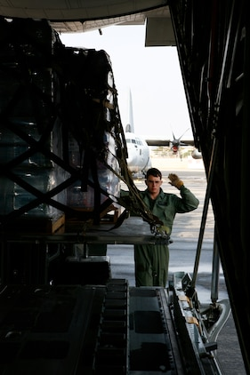 Lance Cpl. Eric M. Wanczak, a Marine Aerial Refueler Transport Squadron 152 loadmaster, guides a forklift operator to get cargo into a C-130 in preparation for a humanitarian mission to Sendai, Japan, as part of Operation Tomodachi here March 25. During this mission, VMGR-152 shuttled approximately 30,000 pounds of water, clothing, food and other miscellaneous relief supplies from Marine Corps Air Station Iwakuni to Sendai, Japan.