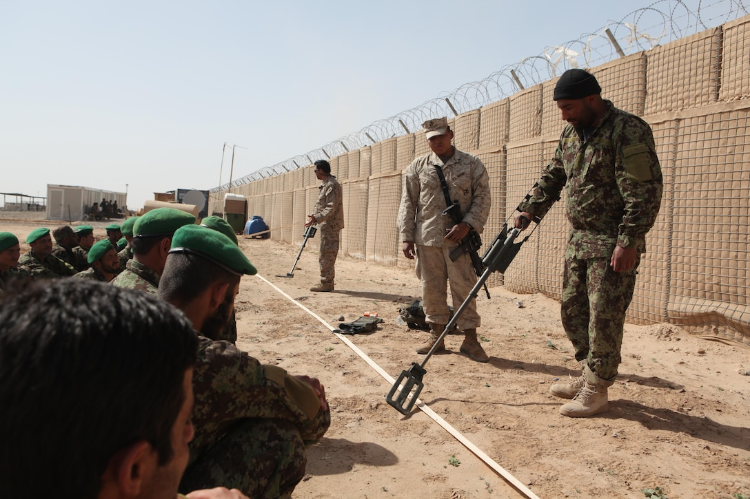 Cpl. Joshua E. Berryhill oversees one Afghan National Army soldiers demonstrating the proper way to mark a possible Improvised Explosive Device threat to his peers. The Broken Arrow, Okla., native is an IED lane advisor with the Embedded Training Team, Regimental Combat Team 1 and teaches two classes a week to the ANA soldiers.