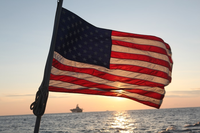 The American flag flies aboard a landing craft utility, launched from the USS Essex (LHD 2), visible in the background at sunrise, March 27. The 31st Marine Expeditionary Unit and Amphibious Squadron 11 delivered food, water, comfort items and commercial repair vehicles to residents on the isolated island of Oeshima using U.S. Navy landing craft, demonstrating the MEU's expeditionary capabilities in ship-to-shore amphibious operations. Marines and Sailors of the 31st MEU are conducting humanitarian aid and disaster relief missions in northeast Japan in coordination with the Japanese Self Defense Forces.
