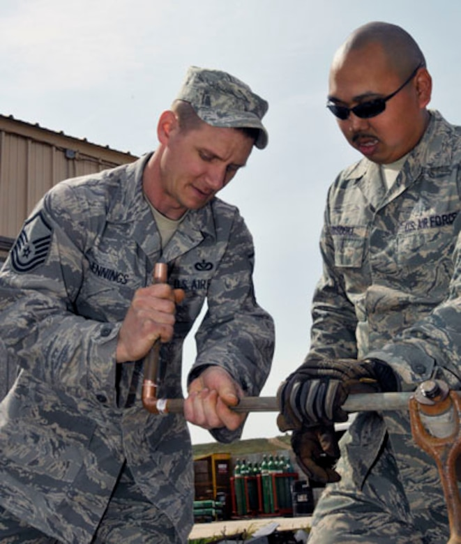 SAN CLEMENTE ISLAND, Calif. -- Master Sgt. Chad Jennings, the supervisor of the Heating, Ventilation, and Air Conditioning Section from the 176th Civil Engineer Squadron, teaches a junior member of his section about preparing pipes for soldering here March 17. 