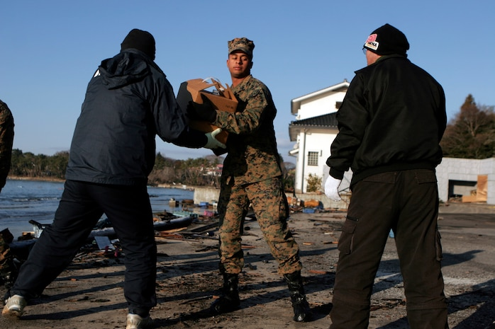 A Marine with the 31st Marine Expeditionary Unit, helps Japanese locals unload a U.S. Navy landing craft here, March 27. The 31st Marine Expeditionary Unit delivered food, water, health and comfort supplies, and Japanese electrical utility vehicles to the isolated island of Oshima, in conjunction with Japanese Self-Defense Forces. The 31st MEU's involvement is part of a larger U.S. government response, after a 9.0 earthquake and subsequent tsunami struck Japan causing widespread damage. The 31st MEU is ready to support our Japanese partners and to provide assistance when called upon.