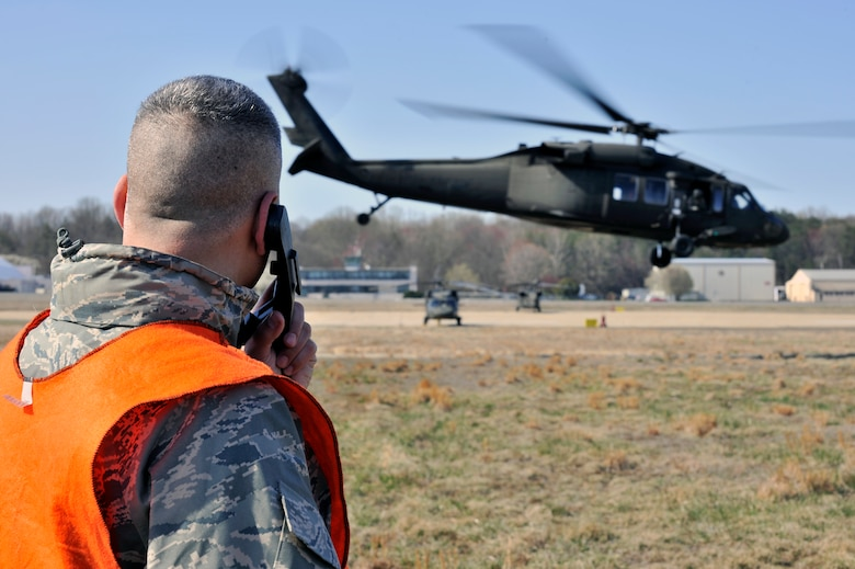 Lt. Col. Kjall Gopaul, Joint and Air Staff acting director, and helicopter deployment readiness training instructor, speaks to the pilots of a UH-60 Black Hawk helicopter, as it takes off during a training exercise March 25, 2011, at Davison Army Airfield, Va. The training is performed once a month and more than 2,000 Airman have completed the training since it began in 2003. (U.S. Air Force Photo by Senior Airman Perry Aston) (Released)