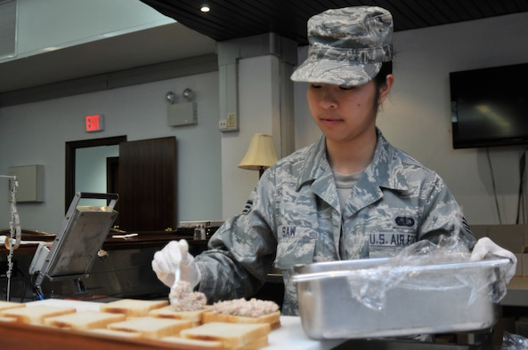313TH AIR EXPEDITIONARY WING -- Senior Airman Kaythi Saw, a flight kitchen employee from Spangdahlem Air Base, Germany, prepares sandwiches for flight meals in support of Joint Task Force Odyssey Dawn March 30. Joint Task Force Odyssey Dawn is the U.S. Africa Command task force established to provide operational and tactical command and control of U.S. military forces supporting the international response to the unrest in Libya and enforcement of United Nations Security Council Resolution (UNSCR) 1973. UNSCR 1973 authorizes all necessary measures to protect civilians in Libya under threat of attack by Gadhafi regime forces. JTF Odyssey Dawn is commanded by U.S. Navy Admiral Samuel J. Locklear, III. (U.S. Air Force photo/Senior Airman David Dobrydney)