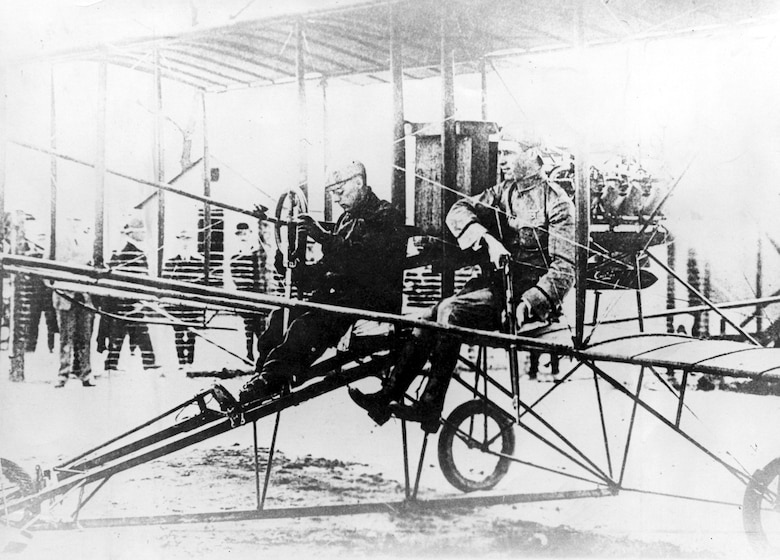 Lt. Fickel demonstrates how he fired the first shot from an airplane. The man at the controls for this historic photograph was Charles F. Willard, a Curtiss pilot. (U.S. Air Force photo)