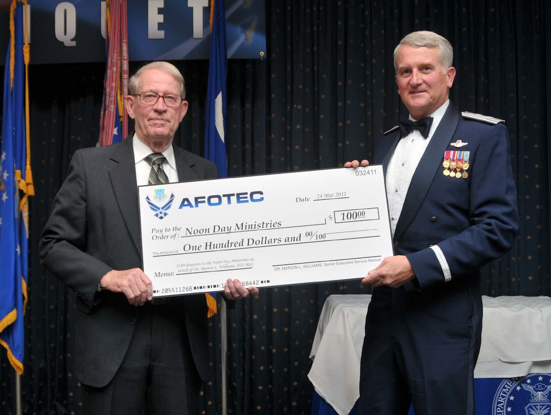 Air Force Operational Test and Evaluation Center Commander Maj. Gen. David J. Eichhorn (right) presents Dr. Marion L. Williams a donation to Noon Day Ministries in his name in appreciation for being a guest speaker at the March 24, 2010 AFOTEC Annual Awards Banquet.