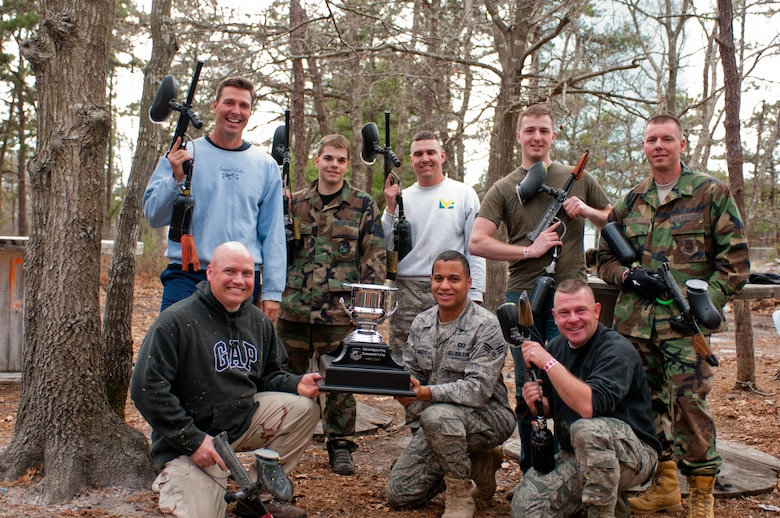 Members of the Air Operations Group pose with the trophy after winning the May Commanders Cup paintball tournament at Cape Cod Paintball grounds.