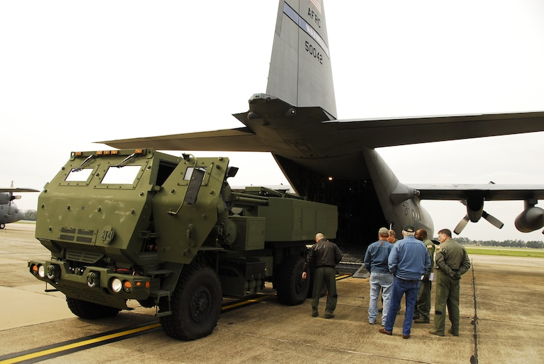 The 908th Airlift Wing recently teamed with the U.S. Army and Lockheed Martin to help increase transport capabilities involving a High Mobility Artillery Rocket System (HIMARS, an artillery rocket platform mounted on a five-ton truck. Above, 908th crew members line up the HIMARS prior to loading it on a C-130.