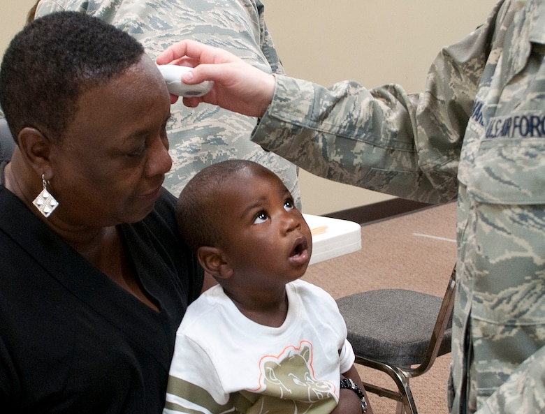 HAYNEVILLE, Ala. -- A young Hayneville resident watchs Master Sgt. Jessica Alvarez take his mother's temperature at a free medical clinic here May 3, 2011. Twenty-five members of the medical group (together with 10 support personnel from other Alaska Air Guard units) arrived here May 1 for 12 days of training through the Innovative Readiness Program. This program allows Guard and Reserve members to get the training they need while at the same time delivering real-world results -- in this case, providing an array of health-care services to a historically underserved area. Alaska Air National Guard photo by Capt. John Callahan.