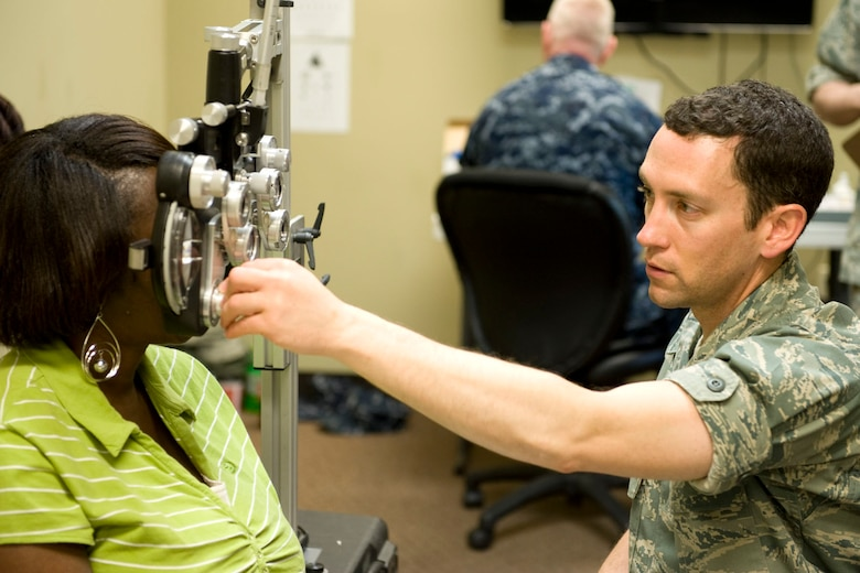 HAYNEVILLE, Ala. - Capt. Andrew Adamich, an optometrist from the 176th Medical Group, Alaska Air National Guard, performs a sight test with a phoropter on a patient to determine her eyeglass prescription, May 3, 2011.  Adamich and about 35 other members from the 176th Wing are in Alabama for an Innovative Readiness Training (IRT) mission. The IRT program allows for real-world training opportunities for military personnel while providing needed services to under-served communities in the United States.  Alaska Air National Guard photo by Master Sgt. Shannon Oleson.