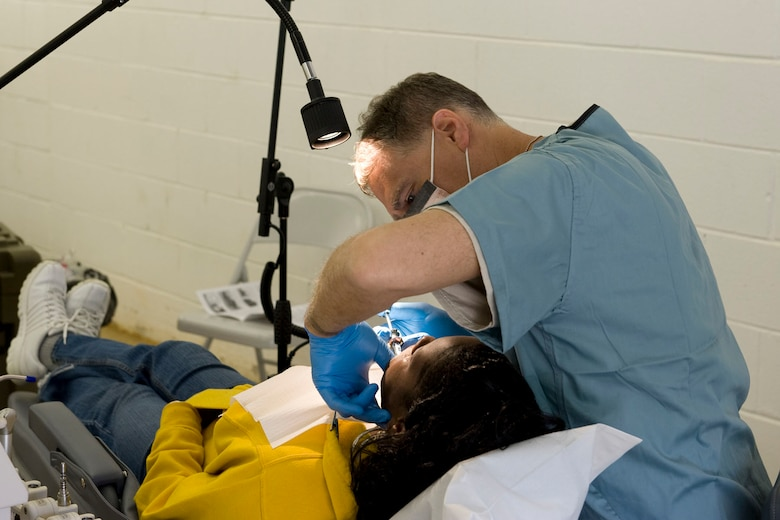 HAYNEVILLE, Ala. - Maj . Michael Majchrowicz, a dentist with the 176th Medical Group, Alaska Air National Guard, works on a patient, May 5, 2011. Majchrowicz and about thirty-five other members from the Wing are in Alabama for an Innovative Readiness Training (IRT) mission.  The IRT program allows for real world training opportunities for military personnel while providing needed services to under-served communities in the United States. The Shower kits will be used by the men of the group during the 10-day mission.  Alaska Air National Guard photo by Master Sgt. Shannon Oleson.