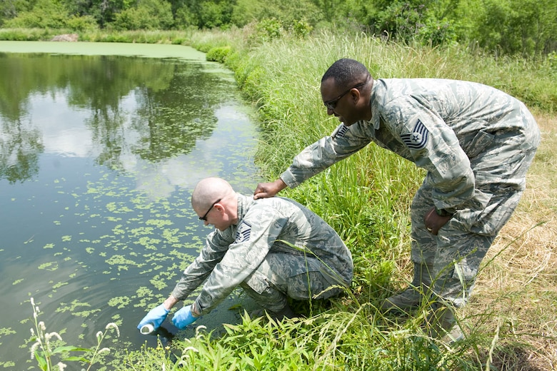 HAYNEVILLE, Ala. - Master Sgt. Ryan Voigt, a a bioenvironmental engineering technician with the 176th Medical Group, Alaska Air National Guard, collects a sample of water from the City of Hayneville?s waste-water treatment lagoon while Tech. Sgt. Dainard Caldwell, a public health technician with group, holds onto him to keep him from falling into the lagoon, May 8, 2011.  Voigt and Caldwell were in Alabama to help test the waste water for permit compliance and related treatment adjustments, and with drinking water for chlorine amount. They were also deploy with another seventy servicemembers from numerous military components and services in Hayneville for an Innovative Readiness Training (IRT) mission. The IRT program allows for real world training opportunities for military personnel while providing needed services to under-served communities in the United States. Alaska Air National Guard photo by Master Sgt. Shannon Oleson.