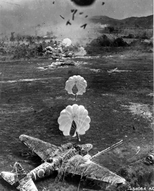 """Seconds after the destruction of a Douglas A-20, the camouflaged Japanese """"Betty"""" bomber was destroyed by parafrag bombs during a low-level attack on the airdrome. (U.S. Air Force photo)"""