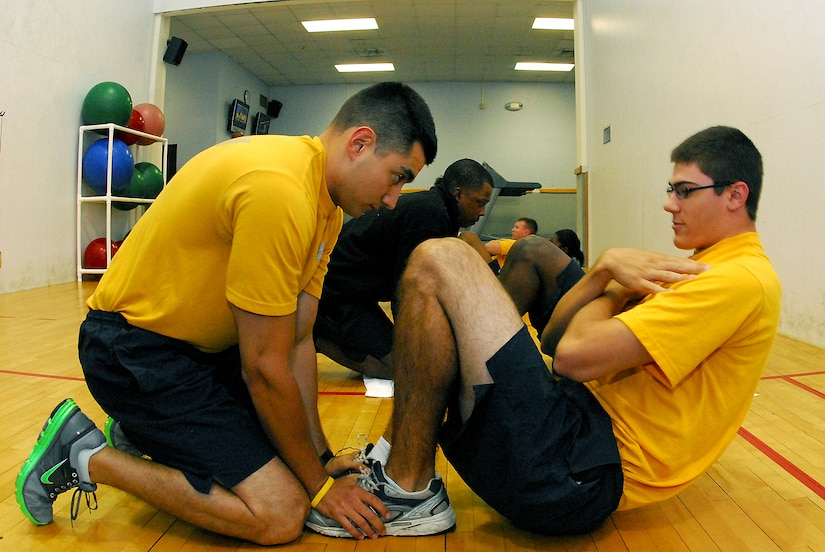 Information Systems Technician Seaman Brian Latour conducts the sit-up portion of his Physical Fitness Assessment as his partner, Machinist's Mate 3rd Class Michael Barbaro, holds his feet and keep count during the bi-annual physical readiness test for Naval Support Activity personnel at Sam's Gym on Joint Base Charleston-Weapons Station.  The PFA, conducted every six months, consists of a cardiovascular test, push-ups and sit-ups examining each Sailor's cardio-respiratory endurance, muscular strength and stamina performance. (U.S. Navy photo/Machinist's Mate 3rd Class Brannon Deugan)
