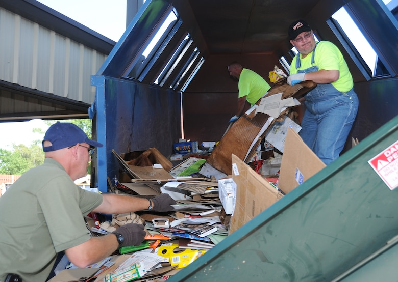 From left, Mr. Robertson, Duane Olson and Douglas Houle work to empty a cardboard recycling bin to prepare the cardboard for binding into bales. Zero Waste Solutions collects a variety of recyclables and sells it to local processing companies.