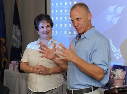 Linda Lankosz listens as Terry Serpico tells a story about his father to a captive audience at the Military Spouses' Appreciation Tea on Joint Base Charleston, May 7. Mr. Serpico plays the character Col. Frank Sherwood on the television series Army Wives. He volunteered to talk and take pictures with the military spouses during the event. The Tea was sponsored by the Airmen and Family Readiness Center to show appreciation for the military spouses.  Some of the activities included gift giveaways, crafts, and make-overs given by professional salon volunteers. Mrs. Lankosz is a community readiness consultant at the Airmen and Family Readiness Center.  (U.S. Air Force photo/ Staff Sgt. Nicole Mickle)