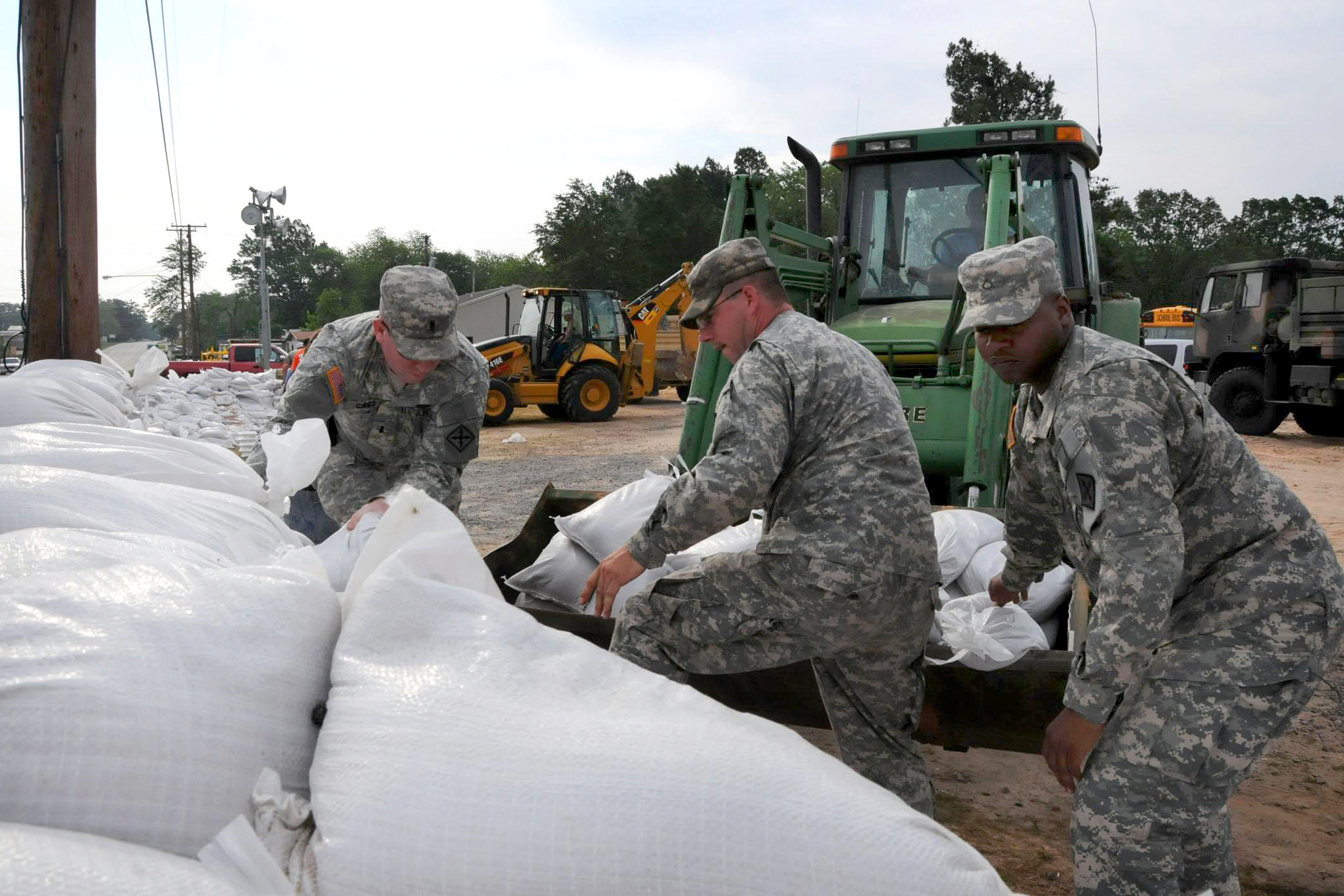 Army soldiers place sandbags in areas affected by flooding from the