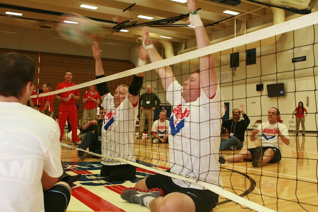 Veteran Marines Travis Greene and Richard Bacchus (left to right) put up a fight to block a shot during a volleyball scrimmage against Colorado community leaders.  The event allowed the Marine athletes to practice and showcase their skills for the upcoming Warrior Games.  The Games will be held at the Olympic Training Center in Colorado Springs, Colo. May 16-21.